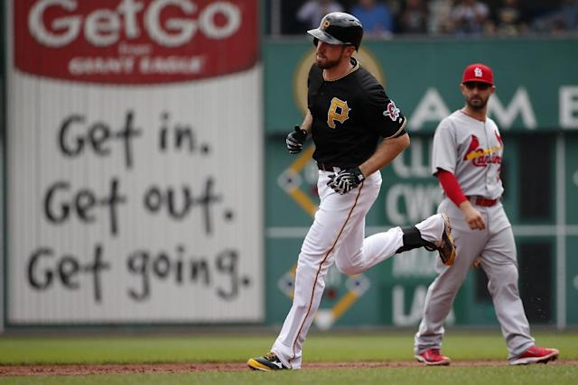 Pittsburgh Pirates' Ike Davis, center, rounds second past St. Louis Cardinals second baseman Daniel Descalso after hitting a two-run home run off St. Louis Cardinals' starting pitcher Adam Wainwright during the second inning of a baseball game in Pittsburgh Wednesday, Aug. 27, 2014. (AP Photo/Gene J. Puskar)