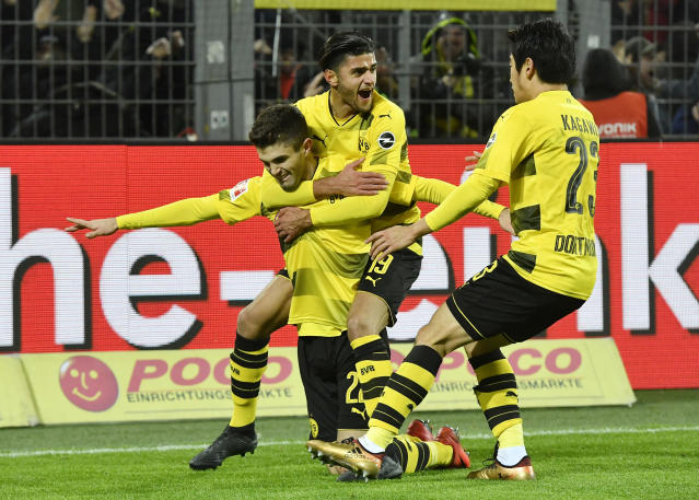 "<a class=""link rapid-noclick-resp"" href=""/soccer/teams/borussia-dortmund/"" data-ylk=""slk:Borussia Dortmund"">Borussia Dortmund</a>'s <a class=""link rapid-noclick-resp"" href=""/soccer/players/christian-pulisic/"" data-ylk=""slk:Christian Pulisic"">Christian Pulisic</a> is mobbed by teammates after scoring the winner against Hoffenheim. (AP Photo/Martin Meissner)"