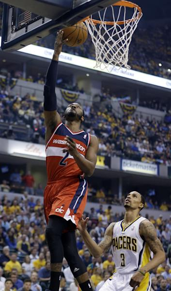 Washington Wizards' John Wall (2) puts up a shot over Indiana Pacers' George Hill (3) during the first half of game 5 of the Eastern Conference semifinal NBA basketball playoff series Tuesday, May 13, 2014, in Indianapolis. (AP Photo/Darron Cummings)