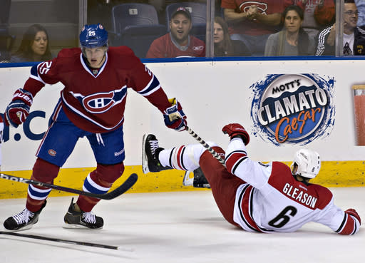 Montreal Canadiens' Michael McCarron, left, pulls his stick from Carolina Hurricanes' Tim Gleason during the first period of a preseason NHL hockey game Friday, Sept. 20, 2013, in Quebec City. (AP Photo/The Canadian Press, Jacques Boissinot)