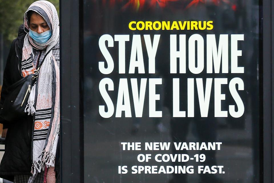 LONDON, UNITED KINGDOM - 2021/01/10: A woman walks past the Government's 'Stay Home, Save Lives' Covid-19 publicity campaign poster in London, as the number of cases of the mutated variant of the SARS-Cov-2 virus continues to spread around the country. (Photo by Dinendra Haria/SOPA Images/LightRocket via Getty Images)