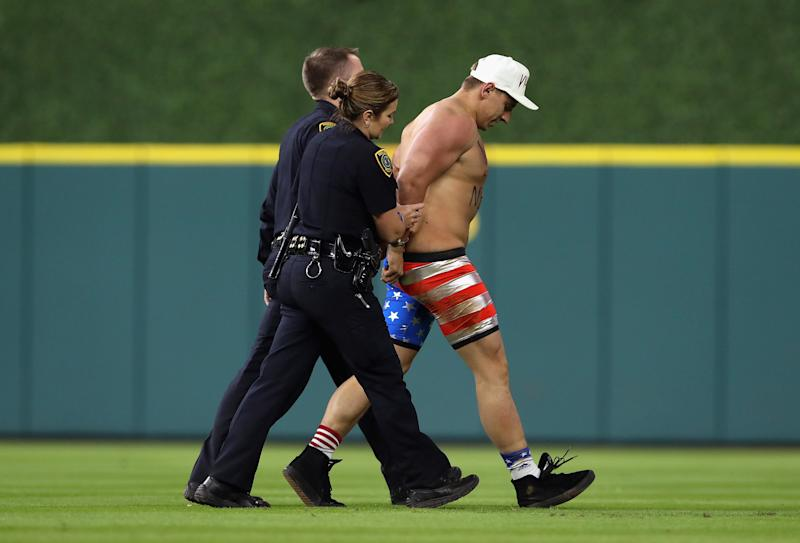 Security workers escort Vitaly Zdorovetskiy off the field. (Christian Petersen/Getty Images)