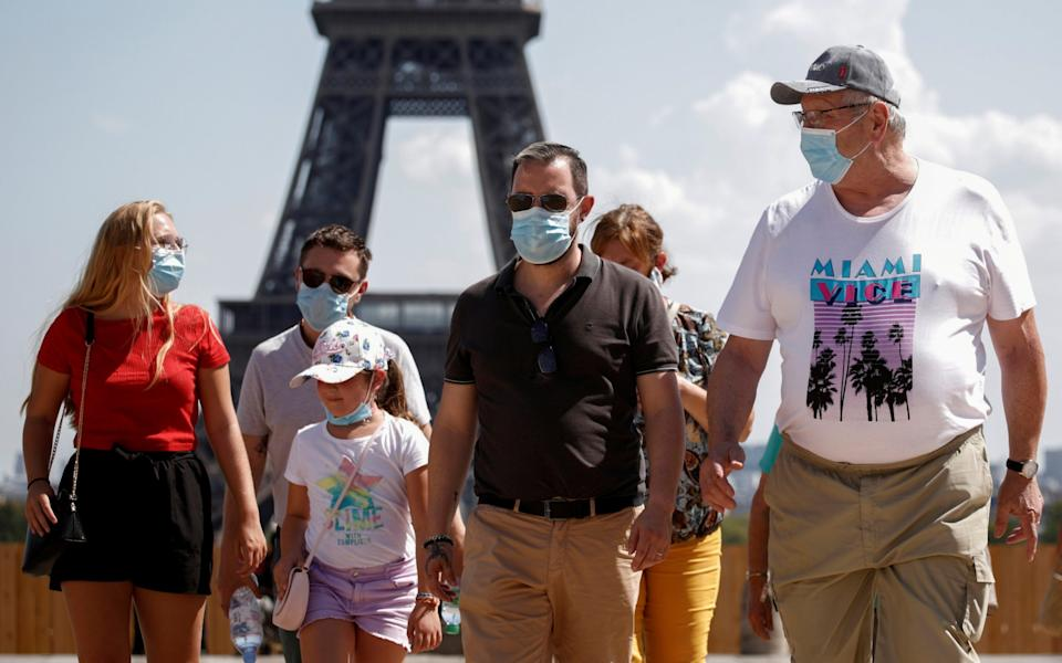 People wearing protective face masks walk at the Trocadero square near the Eiffel Tower in Paris, France - Benoit Tessier / Reuters