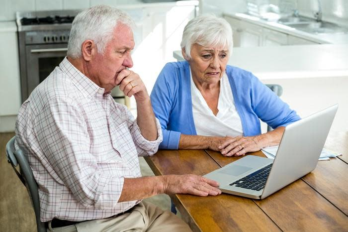 Senior couple seated at a table, staring at a laptop with worried expressions