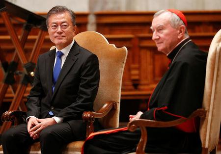 South Korean President Moon Jae-in sits with Italian cardinal Pietro Parolin at the end of a special mass for peace in the Korean peninsula in Saint Peter's Basilica at the Vatican