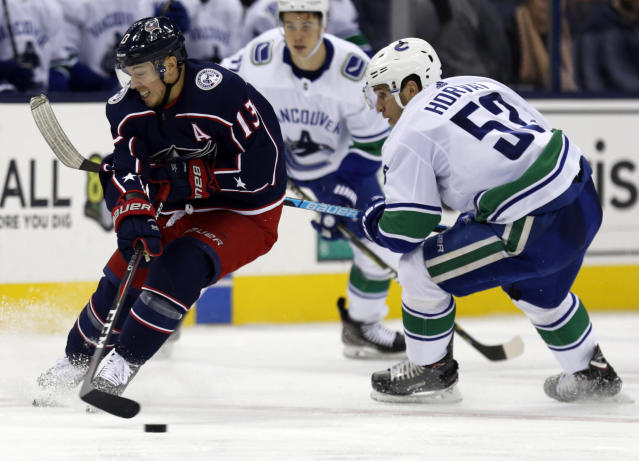 Columbus Blue Jackets forward Cam Atkinson, left, passes the puck against Vancouver Canucks forward Bo Horvat during the second period of an NHL hockey game in Columbus, Ohio, Tuesday, Dec. 11, 2018. (AP Photo/Paul Vernon)