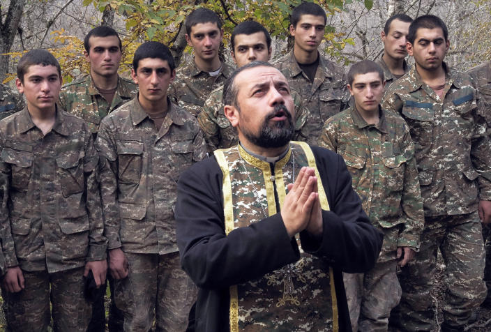 Priest Sebeos Galachyan conducts a baptism ceremony for ethnic Armenian soldiers in a military camp near the front line during a military conflict in separatist region of Nagorno-Karabakh, Monday, Nov. 2, 2020. Fighting over the separatist territory of Nagorno-Karabakh entered sixth week on Sunday, with Armenian and Azerbaijani forces blaming each other for new attacks. (AP Photo)
