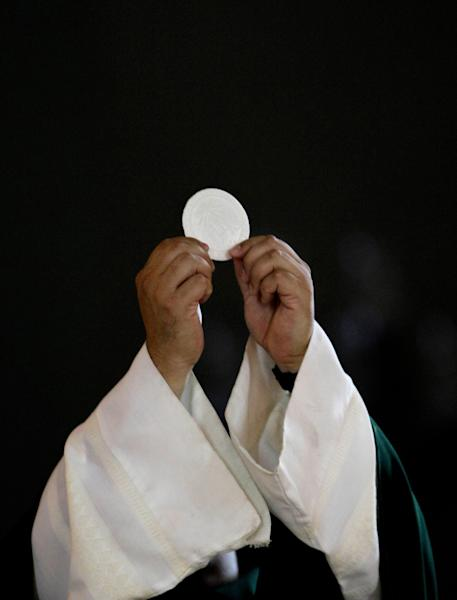 """In this May 29, 2013 photo, a priest holds up a host as he celebrates Mass at Catholic a church in Caracas, Venezuela. Church officials say food shortages and foreign exchange restrictions are causing a lack of ingredients needed to celebrate Mass: altar wine as well as wheat to produce communion wafers. """"We only have enough for two months,"""" said Archbishop Roberto Luckert, a spokesman for the Venezuelan Episcopal Conference. (AP Photo/Fernando Llano)"""