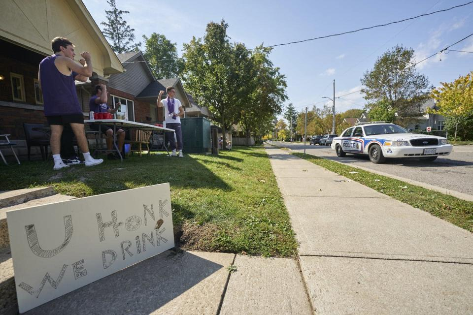 A police car passes a student house where people are drinking outside.