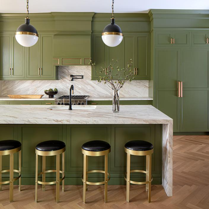"""A leak led to an unplanned kitchen renovation. Floors were refinished in Rubio, which gave the wood a contemporary matte finish. Lindsay originally wanted to paint the cabinets oxblood red, but after happening across Farrow & Ball's Bancha green, she changed her plans. """"I immediately felt like that was the right color, and it just brought nature in,"""" she says. The leather and brass stools are by Noir."""