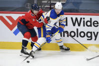 Buffalo Sabres center Jack Eichel (9) and Washington Capitals defenseman Nick Jensen (3) battle for the puck during the second period of an NHL hockey game, Friday, Jan. 22, 2021, in Washington. (AP Photo/Nick Wass)