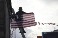 A man hangs a US flag up in the town of Ballina, North West of Ireland, Saturday, Nov. 7, 2020. Ballina is the ancestral home of US President elect Joe Biden. Biden was elected Saturday as the 46th president of the United States, defeating President Donald Trump in an election that played out against the backdrop of a pandemic, its economic fallout and a national reckoning on racism. (AP Photo/Peter Morrison)