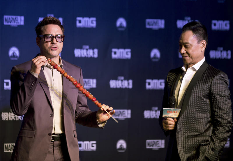 """U.S. actor Robert Downey Jr. tries out """"bingtanghulu,"""" a traditional Chinese snack, next to Chinese actor Wang Xueqi, right, during a world premiere event of his new movie """"Iron Man 3"""" at a Beijing hotel Saturday, April 6, 2013. (AP Photo/Andy Wong)"""