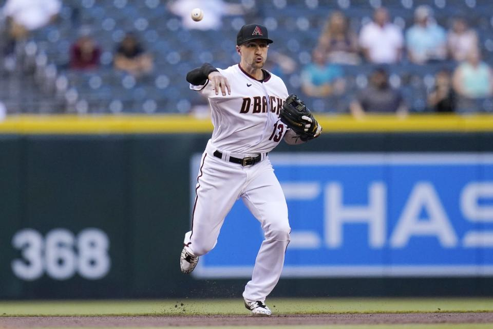 Arizona Diamondbacks shortstop Nick Ahmed throws to first base to get Miami Marlins' Adam Duvall out during the first inning of a baseball game Thursday, May 13, 2021, in Phoenix. (AP Photo/Ross D. Franklin)