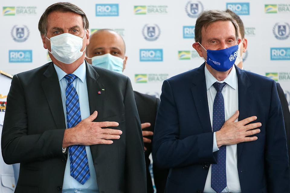 RIO DE JANEIRO, BRAZIL - AUGUST 14: (L-R) President of Brazil Jair Bolsonaro and the Mayor of Rio de Janeiro Marcelo Crivella stand for the national anthem during the opening of the Escola Civico-Militar General Abreu on August 14, 2020 in Rio de Janeiro, Brazil. The civic-military school inaugurated by the city of Rio de Janeiro has a capacity for 500 students. Two other units will be added to the complex, which will be launched by the end of the year. Civic-military schools are non-militarized institutes with retired military agents as tutors, a model advocated by the government of Jair Bolsonaro. (Photo by Buda Mendes/Getty Images)