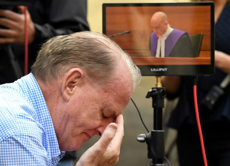 A man reacts as he listens to County Court Chief Judge Peter Kidd, on a monitor speak, during the sentencing of Cardinal George Pell who was was found guilty on historic child sex crimes.