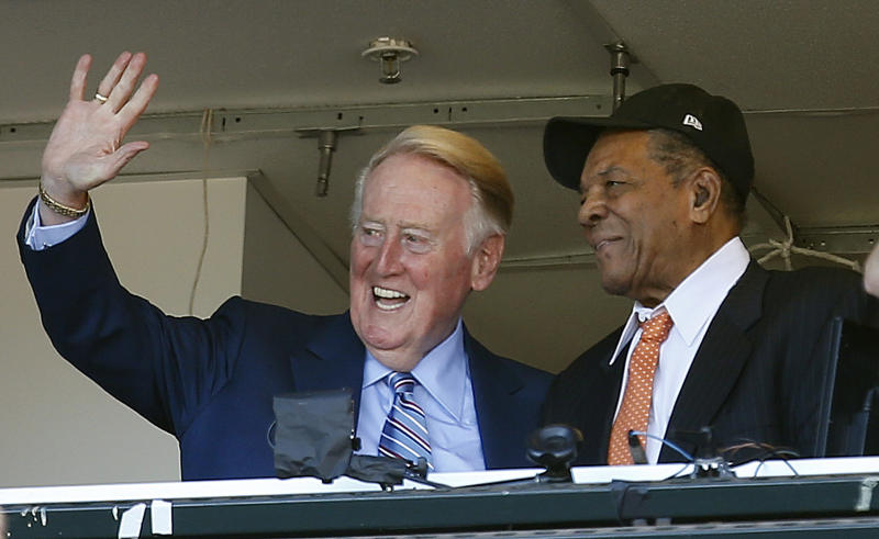 FILE - In this Oct. 2, 2016, file photo, Los Angeles Dodgers announcer Vin Scully waves to fans alongside Hall of Famer baseball player Willie Mays during the fourth inning of a baseball game between the San Francisco Giants and the Los Angeles Dodgers in San Francisco. On Monday, April 3, 2017, the Dodgers will play their first opening day since 1950 without Scully calling their games. He won't be in the stands. He won't make a point of watching on TV, either. (AP Photo/Tony Avelar, File)