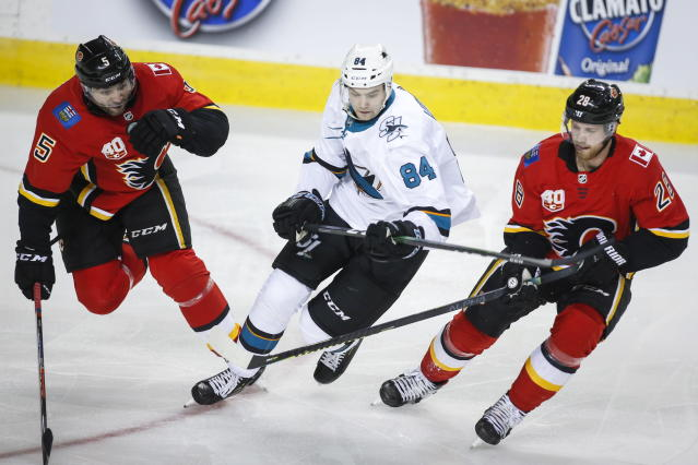 San Jose Sharks' Maxim Letunov, centeer, gets past Calgary Flames' Mark Giordano , left, and Elias Lindholm during the second period of an NHL hockey game, Tuesday, Feb. 4, 2020 in Calgary, Alberta. (Jeff McIntosh/The Canadian Press via AP)