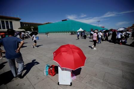 A tourist rests under an umbrella next to the installations set up on Tiananmen Square for the 70th anniversary of the founding of People's Republic of China in Beijing