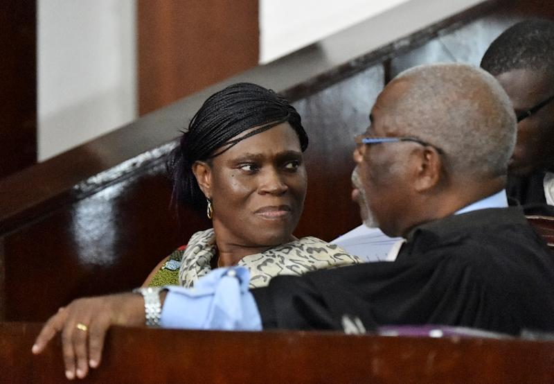 Simone Gbagbo talks to her lawyer at the Abidjan's courthouse on October 10, 2016 (AFP Photo/Sia Kambou)