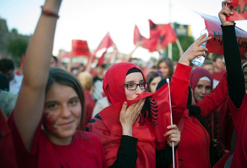 A woman kisses the Albanian flag during a protest on the streets of Skopje, Macedonia on June 13, 2015 (AFP Photo/Robert Atanasovski)