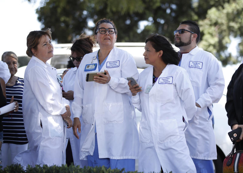 Hospital staff wait outside after they were evacuated from Kaiser Permanente Downey Medical Center, following reports of someone with a weapon at the facility in Downey, Calif., Tuesday, Sept. 11, 2018. Los Angeles County sheriff's officials say a suspect is in custody and deputies and police officers are methodically searching the complex. (AP Photo/Jae C. Hong)