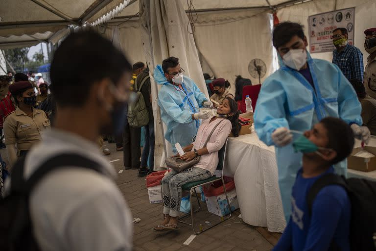 Health workers take nasal swab samples of passengers to test for COVID-19 at a bus terminal in New Delhi, India, Wednesday, March 24, 2021. (AP Photo/Altaf Qadri)