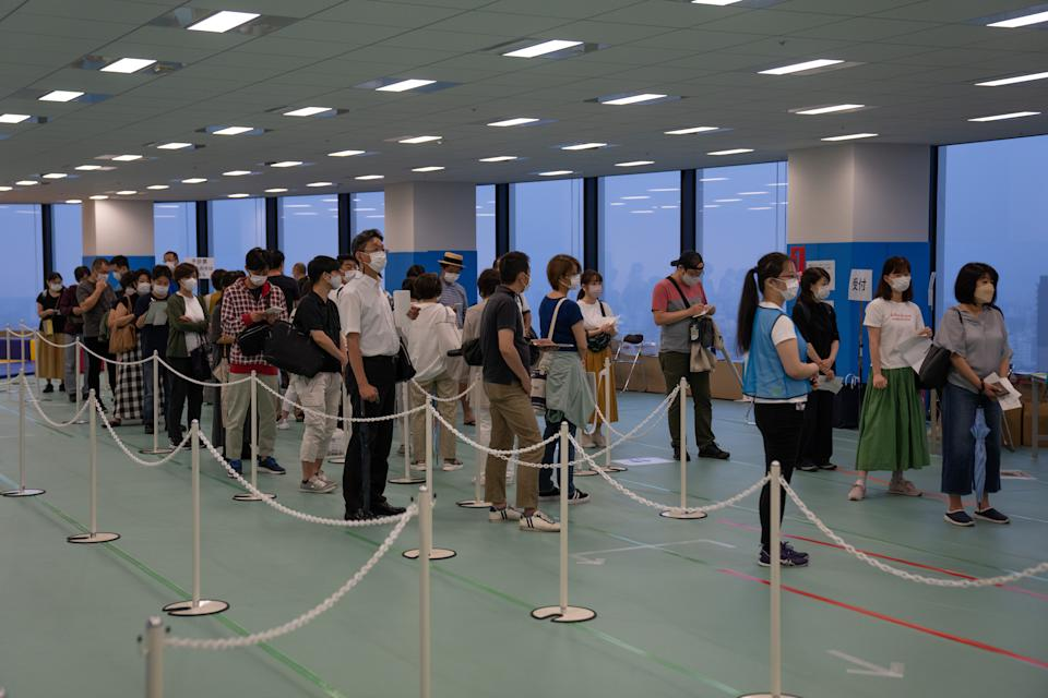 People line up to register for a dose of the Moderna vaccine on June 30 in Tokyo. The Japanese government has begun an after-hours vaccination campaign as it expands its coronavirus inoculation drive to include younger people. (Carl Court/Getty Images)