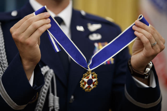 A U.S. Air Force military aide holds the Presidential Medal of Freedom to be presented to former NBA basketball player and general manager Jerry West by President Donald Trump, in the Oval Office of the White House, Thursday, Sept. 5, 2019, in Washington. (AP Photo/Alex Brandon)