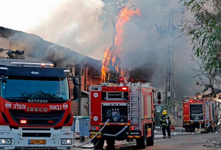 Israeli firefighter trucks douse a burning factory in the southern Israeli town of Sderot, after it was reportedly hit with rockets fired from the Gaza Strip on Tuesday. Israel's military killed a commander of Palestinian militant group Islamic Jihad in a strike on his home in Gaza early in the morning, prompting retaliatory barrages of rocket fire from the Gaza Strip towards Israel where residents ran to bomb shelters while air raid sirens rang out in various parts of the country.