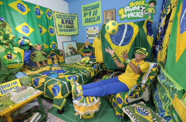 Brazilian soccer fan Marilza Guimaraes da Silva, 63, plays with a ball as she poses for picture, dressed in one of her many outfits matching the colors of the Brazil's national flag (green, yellow, white and blue) at her home in Brasilia May 27, 2014. REUTERS/Joedson Alves (BRAZIL - Tags: SPORT SOCCER WORLD CUP TPX IMAGES OF THE DAY)