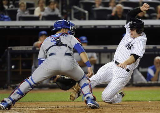 New York Yankees' David Adams, right, scores on a sacrifice fly by Jayson Nix as Toronto Blue Jays catcher J.P. Arencibia waits for the ball during the fifth inning of a baseball game, Friday, May 17, 2013, at Yankee Stadium in New York. (AP Photo/Bill Kostroun)