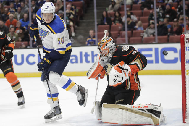 The puck hit by St. Louis Blues' Ryan O'Reilly, not pictured, flies past Blues' Brayden Schenn, left, and Anaheim Ducks goaltender John Gibson for a goal during the first period of an NHL hockey game Wednesday, March 6, 2019, in Anaheim, Calif. (AP Photo/Jae C. Hong)