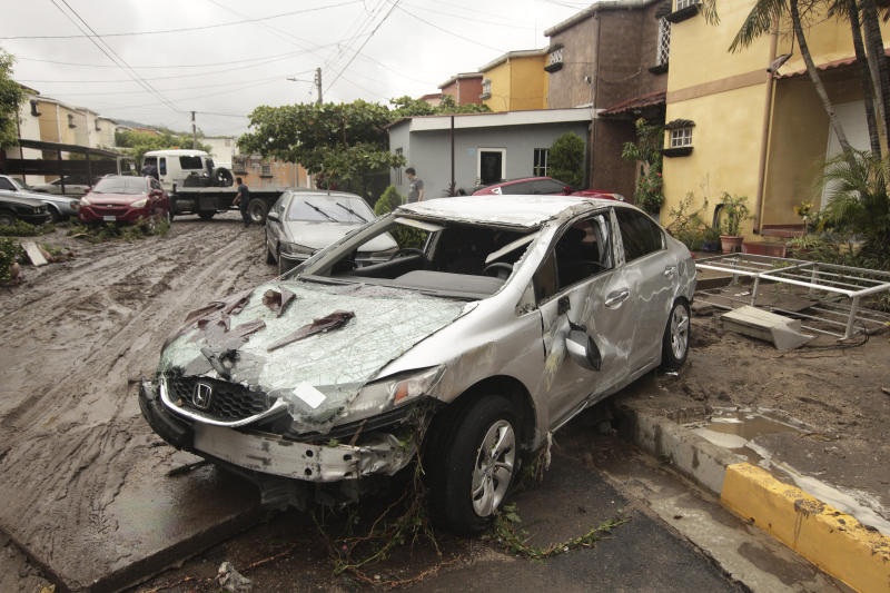 Vehicles stand damaged by the Acelhuate River after a flash flood at a neighborhood in San Salvador, El Salvador, Sunday, May 31, 2020. According to the Ministry of the Interior, at least seven people died across the country after two days of heavy rains. (AP Photo/Salvador Melendez)