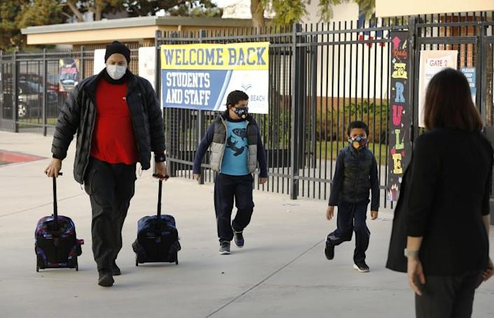 REDONDO BEACH, CA - FEBRUARY 02: Father Luis Aracena helps his two first grade students Knoah Aracena, left and twin brother Kane Aracena with their backpacks as they arrive at Alta Vista Elementary School for the second day of classes as Redondo Beach Unified School district has welcomed back some of its K-2 students this week through a waiver. Alta Vista Elementary School on Tuesday, Feb. 2, 2021 in Redondo Beach, CA. (Al Seib / Los Angeles Times).