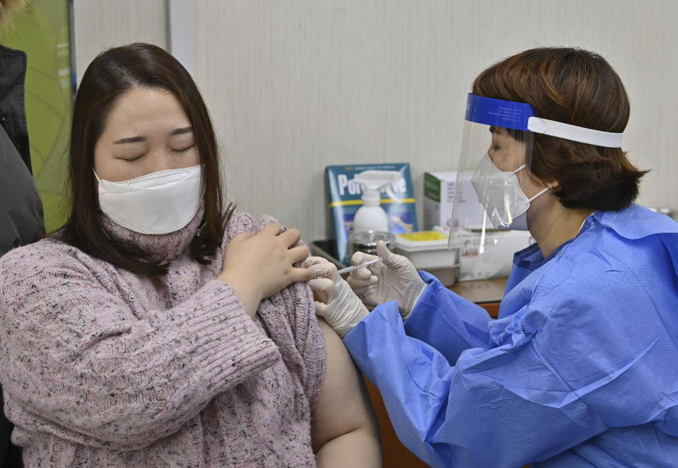 A nursing home worker, left, receives the first dose of the AstraZeneca COVID-19 vaccine at a health care center in Seoul Friday, Feb. 26, 2021. South Korea on Friday administered its first available shots of coronavirus vaccines to people at long-term care facilities, launching a mass immunization campaign that health authorities hope will restore some level of normalcy by the end of the year. (Jung Yeon-je /Pool Photo via AP)