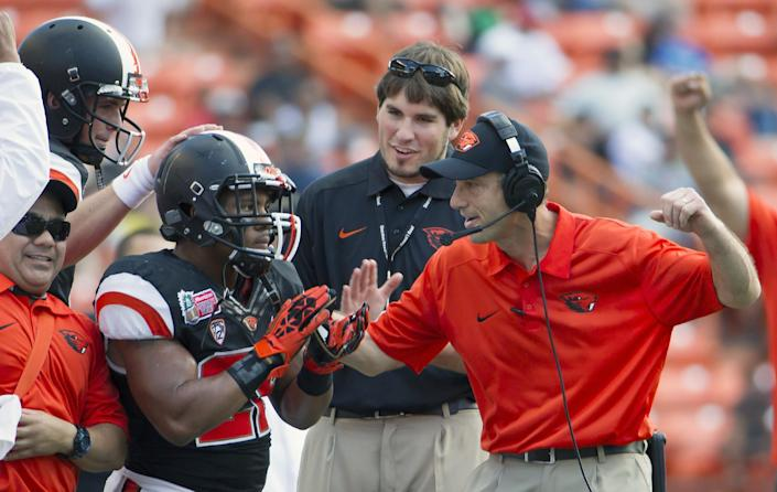 Oregon State head coach Mike Riley, right, congratulates Oregon State running back Terron Ward, center, after the replay official ruled his touchdown good in the second quarter of the Hawaii Bowl NCAA college football game against Boise State, in Honolulu, Tuesday, Dec. 24, 2013. (AP Photo/Eugene Tanner)
