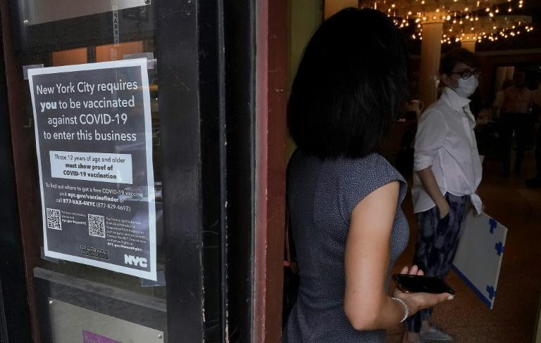 A woman waits to go in a restaurant in New York's Upper West Side on August 17, 2021, the first day where you have to show proof of having a Covid-19 vaccination to participate in indoor dining