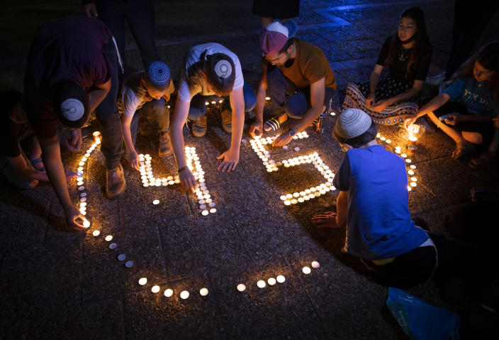 Israeli youths light candles in memory of the 45 ultra-Orthodox Jews killed in a stampede at a religious festival on Friday, during a vigil in Tel Aviv, Israel, Sunday, May 2, 2021. The stampede early Friday had cut short the annual festival of Lag BaOmer on Israel's Mount Meron. The festival had drawn some 100,000 people in the largest gathering. It was one of the country's deadliest civilian disasters. (AP Photo/Oded Balilty)