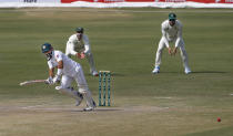 Pakistan's batsman Mohammad Rizwan, left, follows the ball after playing a shot while South Africa's Faf du Plessis, right, and Aiden Markram watches during the second day of the first cricket test match between Pakistan and South Africa at the National Stadium, in Karachi, Pakistan, Wednesday, Jan. 27, 2021. (AP Photo/Anjum Naveed)