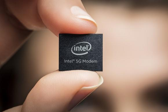 "A person holding a chip that has etched on it ""Intel 5G Modem"""