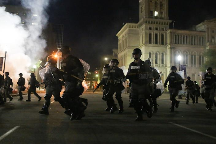"""Riot police run toward protesters after using smoke and stun grenades to clear Jefferson Square Park. <p class=""""copyright"""">Daniel Shular</p>"""