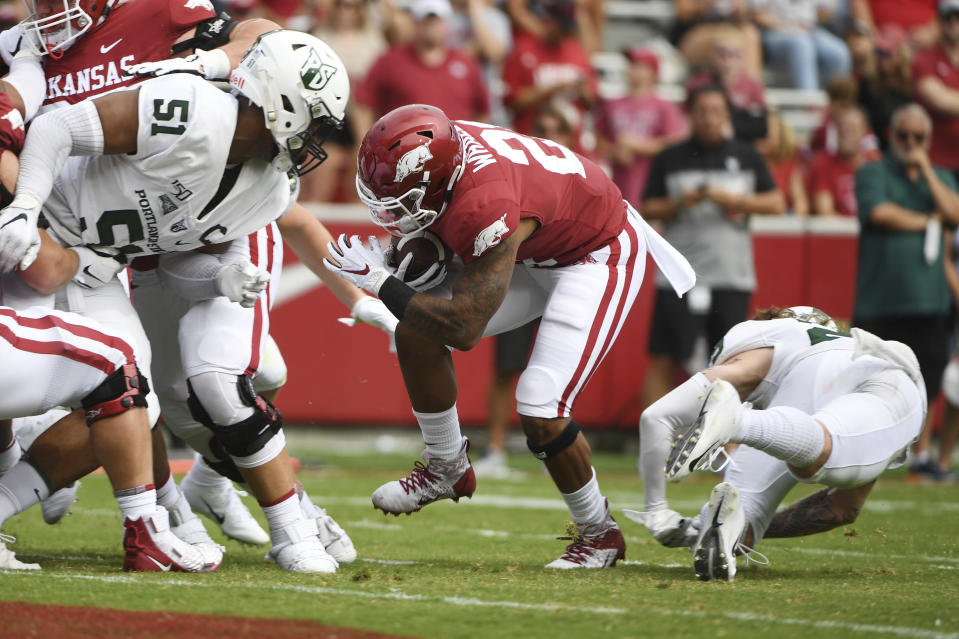 Arkansas running back Devwah Whaley (21) slips past Portland State defender Kenton Bartlett (51) to score a touchdown in the first half of an NCAA college football game, Saturday, Aug. 31, 2019 in Fayetteville, Ark. (AP Photo/Michael Woods)