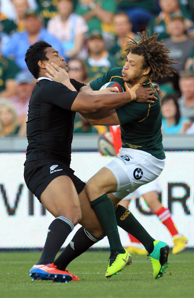 New Zealand's Julian Savea, left, challenges South Africa's Zane Kirchner, right, during their Rugby Championship match at Ellis Park Stadium in Johannesburg, South Africa, Saturday, Oct. 5, 2013. (AP Photo/Themba Hadebe)