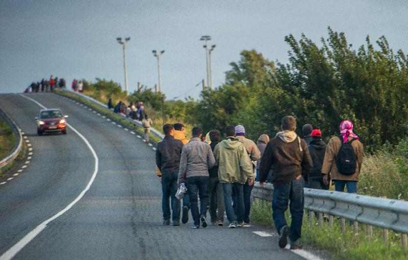 Migrants walk along a road near the Eurotunnel terminal to try to climb in a shuttle heading to Great Britain, on July 28, 2015 in Frethun, northern France (AFP Photo/Philippe Huguen)