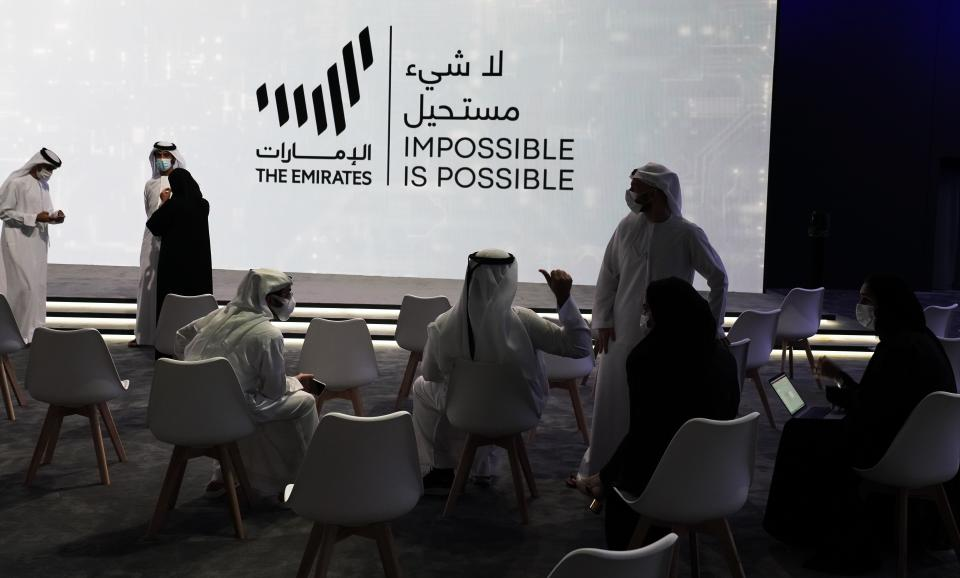 Emiratis talk before an event announcing new economic programs in the United Arab Emirates in Dubai, United Arab Emirates, Sunday, Sept. 5, 2021. The United Arab Emirates announced Sunday a major plan to stimulate its economy and liberalize stringent residency laws for expatriates, as the country seeks to overhaul its finances and attract foreign residents and capital. (AP Photo/Jon Gambrell)
