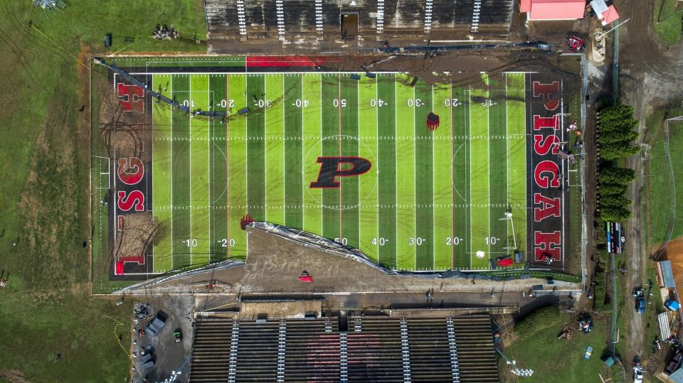 In this image taken with a drone, volunteers clear debris and try to salvage athletic equipment Thursday, Aug. 19, 2021 at Pisgah High School in Canton, N.C., after remnants from Tropical Storm Fred caused flooding in parts of Western North Carolina Tuesday. (Travis Long/The News & Observer via AP)