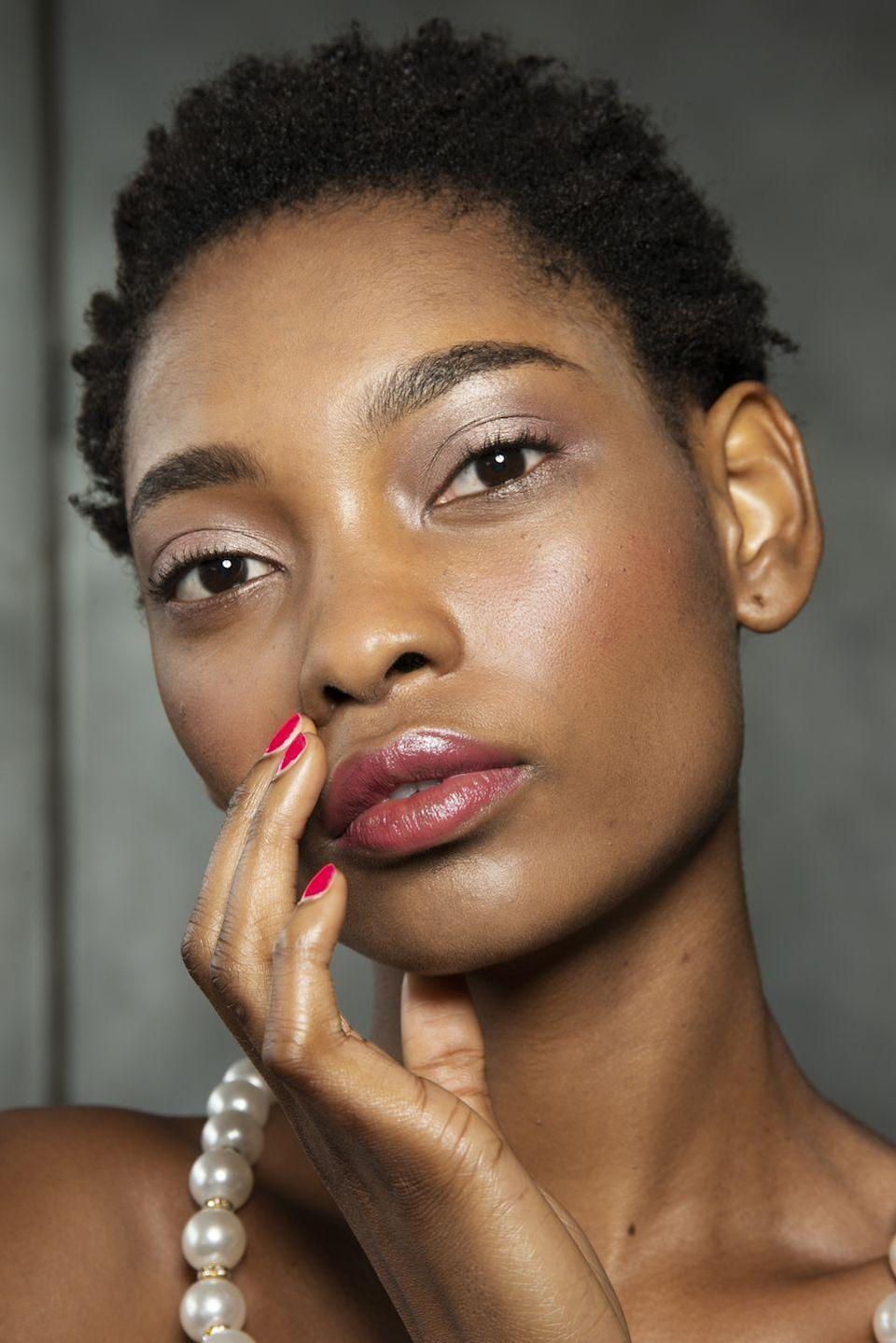 <p>A wash of soft metallic eyeshadow got a sweet and feminine touch thanks to sheer berry lips and red nails.</p>
