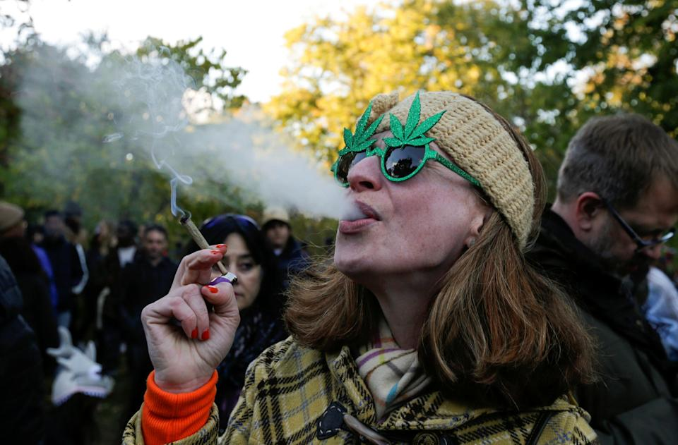 A woman smokes a joint on the day Canada legalizes recreational marijuana at Trinity Bellwoods Park, in Toronto, Ontario, Canada, October 17, 2018. REUTERS/Carlos Osorio
