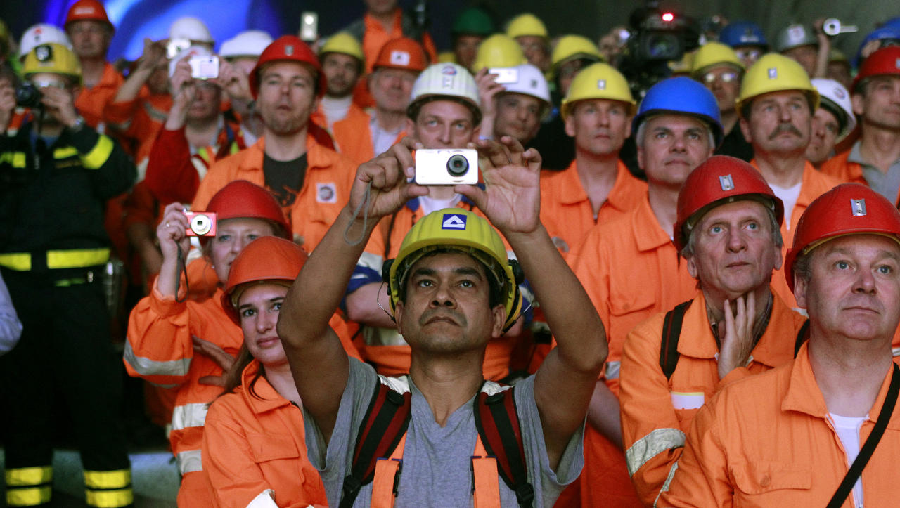 Miners and visitors take pictures as a giant drill machine breaks through the rock at the western tunnel section Sedrun-Faido, at the construction site of the NEAT Gotthard Base Tunnel March 23, 2011. Crossing the Alps, the world's longest train tunnel should become operational at the end of 2016. The project consists of two parallel single track tunnels, each of a lenght of 57 km (35 miles).  REUTERS/Arnd Wiegmann (SWITZERLAND - Tags: BUSINESS TRAVEL EMPLOYMENT) - RTR2KANI